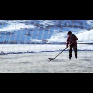 Royalty Free Stock Footage of Young boy playing hockey outdoors; about to score.