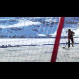 Royalty Free Stock Footage of Young boy about to make a goal playing hockey outdoors.