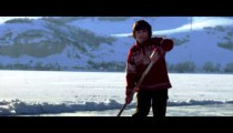 Royalty Free Stock Footage of Young boy playing hockey on an outdoor ice rink.