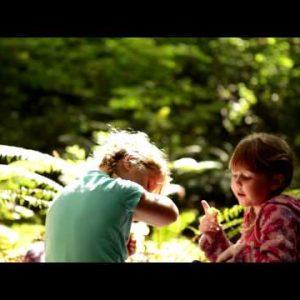 Little girls playing on forest floor