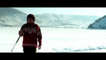 Royalty Free Stock Footage of Young boy in a red sweater walking onto a frozen pond to play hockey.