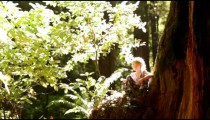 Little girl playing with clover at base of giant pine tree
