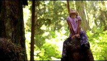 Little girl impressed with tall pine trees
