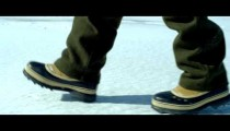 Royalty Free Stock Footage of Snow boots walking across a snow-covered ground.