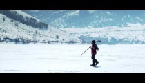 Royalty Free Stock Footage of Young person walking through snow with hockey gear.