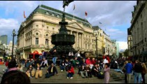People sit on the steps of the Shaftesbury Monument in Piccadilly Circus in London.