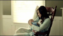Royalty Free Stock Footage of Mother rocking her baby to sleep in a rocking chair.