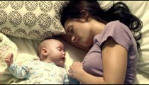 Royalty Free Stock Footage of Mother and baby taking a nap together.