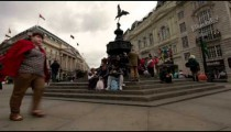 People sit on the steps of the Eros statue in London.