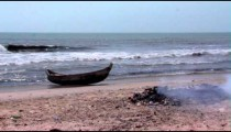 Boat on a beach in Africa with a fire in the foreground.