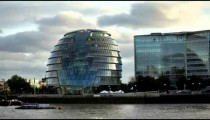 London City Hall building from across River Thames with birds flying over water in foreground.