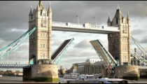 Boat passes through Tower Bridge with bascules raised in London