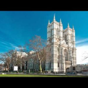 Time-lapse of Westminster Abbey under a blue sky in London.