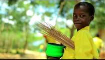 Little smiling Kenyan boy carrying straw and a bucket.