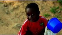 Little Kenyan boy holding a stick and a bucket.