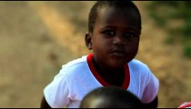 Another Kenyan boy hiding behind another boy.