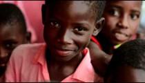 Kenyan boys smiling and pointing at the camera.