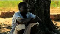 Kenyan boy sitting under a tree, thinking.