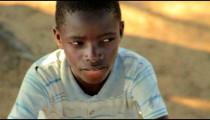 Kenyan boy in a striped shirt looking at the camera.