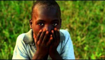 Little Kenyan boy with hands on hips looking at the camera.