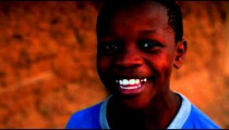 Little Kenyan boy in a blue shirt laughing and smiling.