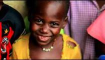 Young Kenyan girl looking and smiling at the camera.