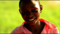 Young Kenyan girl laughing and smiling near a tree.
