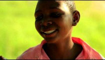 Other Young Kenyan girl laughing and smiling near a tree.