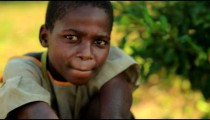 Little Kenyan girl with hands on knees looking at the camera.