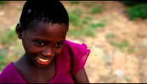Kenyan girl looking between the camera and the ground.