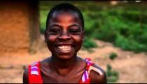 Kenyan girl smiling and laughing at the camera.