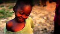 Kenyan girl with large shirt looking at the camera.