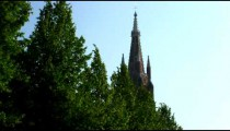 Royalty Free Stock Footage of Church tower over trees in Brugge, Belgium.