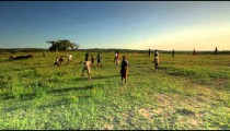 Kids playing soccer in a field in Africa.