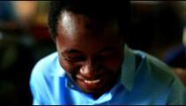 Kenyan teen boy smiles at the camera then laughs.