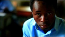 Kenyan student looks at the camera and his school work.