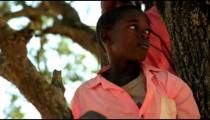 Two kids in a tree in Kenya, Africa.