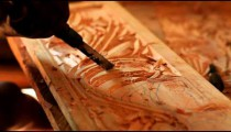 Man chiseling designs in wood in Kenya.