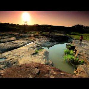 Three boys walking down a dry riverbed in Kenya.