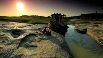 Kids washing clothes in a river in Kenya at sunset.
