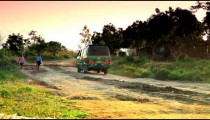 Green van driving on a dirt road near a village in Africa.