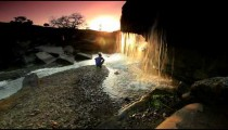 Child watching a waterfall and tossing a rock at sunset in Kenya.