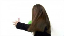 Royalty Free Stock Footage of Young girl playing catch with a green ball on white.