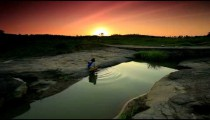 Kenyan child being washed by a woman in a river.