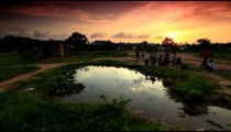 Boys playing at village water hole at sunset in Africa.