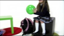 Royalty Free Stock Footage of Pan shot of young twin girls playing catch with a green ball.