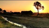 Dirt road and homes in Kenya at sunset.