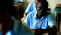 School boy reading a book in class then looking at the camera in Kenya.