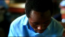 Close up of a student reading, then smiling, in class in Kenya.