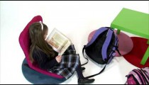 Royalty Free Stock Footage of Young girl reading a book and smiling on white.